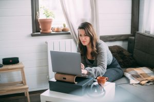 A woman sits in the bedroom with a laptop.